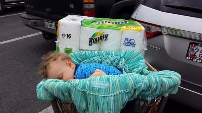 The author's son asleep in a grocery cart